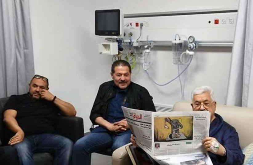 Mahmoud Abbas reads a newspaper in a hospital in the Palestinian city of Ramallah (photo credit: Courtesy)