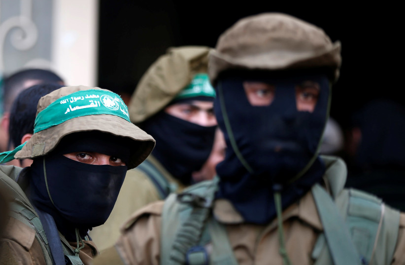 Hamas militants attend the funeral of members of Palestinian security forces loyal to Hamas, in the central Gaza Strip March 22, 2018. (photo credit: REUTERS/MOHAMMED SALEM)
