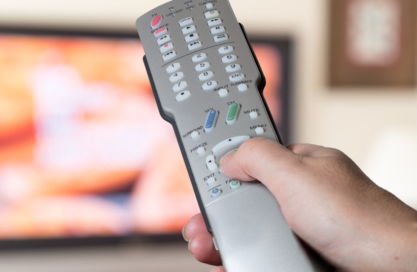 Silver television remote control being pressed by thumb with out of focus screen background (Illustrative) (photo credit: INGIMAGE)