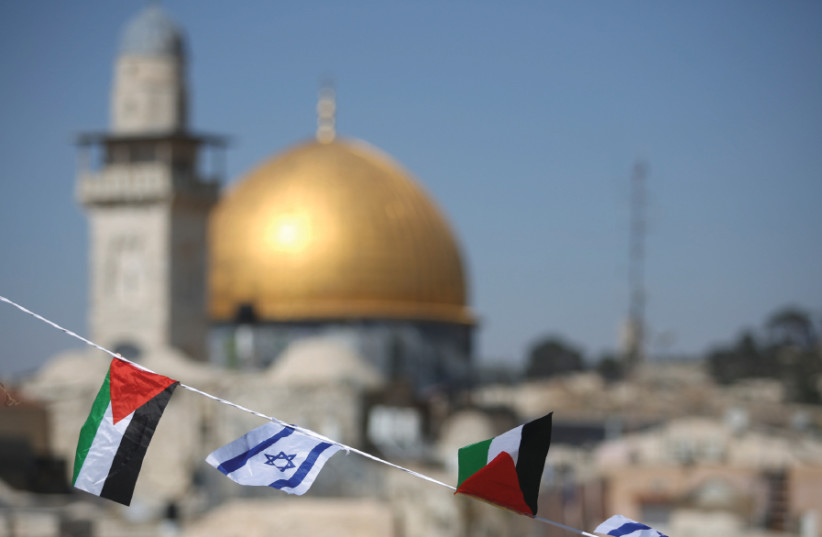 PALESTINIAN AND Israeli flags fly over the Western Wall and the Dome of the Rock (photo credit: MARC ISRAEL SELLEM)