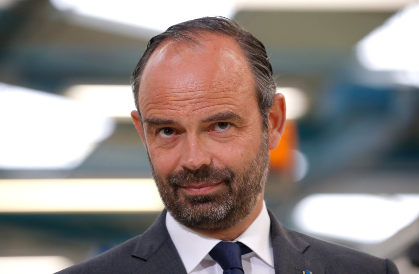 French Prime Minister Edouard Philippe listens to a speech about the government's recycling program during a visit at the Groupe Seb Moulinex factory in Mayenne, France, April 23, 2018. (photo credit: STEPHANE MAHE / REUTERS)