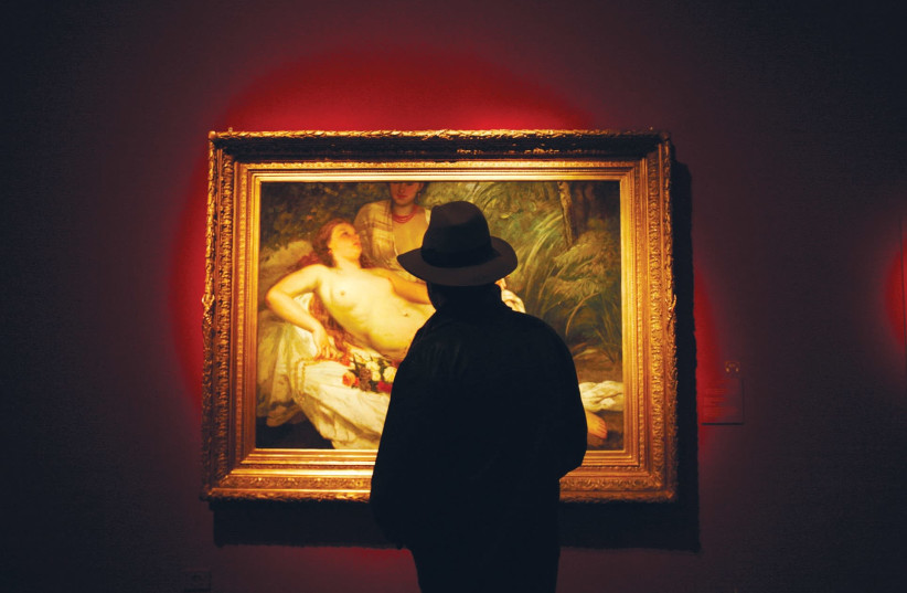 A MAN looks at a painting titled 'The Bathers' during a 2008 exhibition devoted to finding owners of paintings looted by the Nazis. (photo credit: REUTERS)