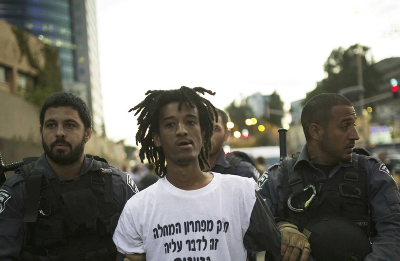 ISRAEL POLICE detain a protester during a 2015 anti-racism demonstration in Tel Aviv. (photo credit: AMIR COHEN/REUTERS)