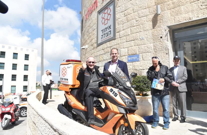 Alan Dershowitz sits on an Ambucycle with United Hatzala founder Eli Beer in Jerusalem (photo credit: Courtesy)