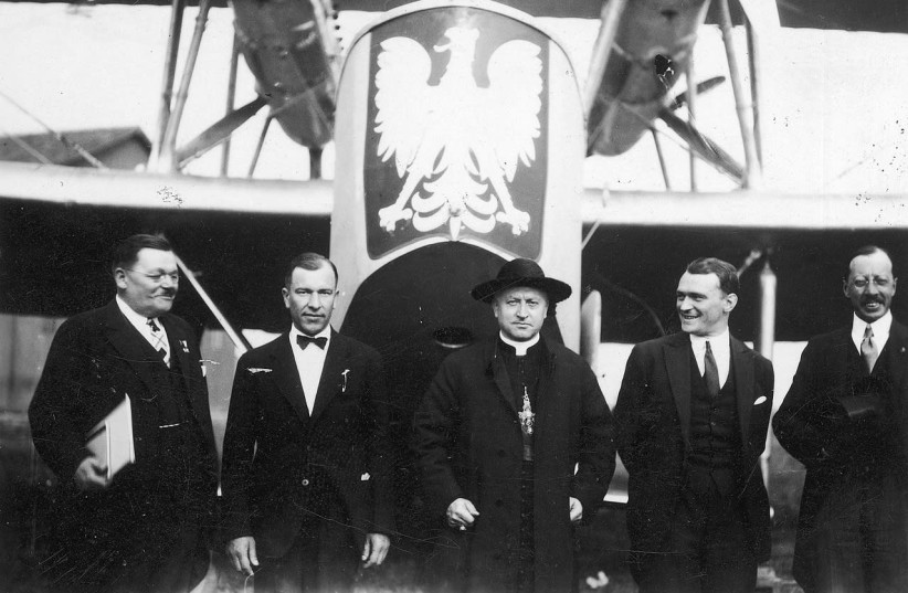 """A photo from 1929 at a dedication of a plane purchased by the Polish consulates. Visible: Cardinal August Hlond (in the center), American Polonia activist Adamkiewicz (1st from left), Lieutenant Reserve Pilot from PLL """"Lot"""" Włodzimierz Klisz (2nd from the left), captain pilot from the 3rd Air Regime (photo credit: Wikimedia Commons)"""