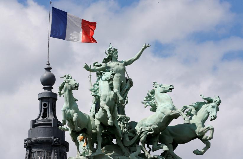 The French flag flies above the Grand Palais in Paris, France, June 24, 2017. (photo credit: REUTERS/JEAN-PAUL PELISSIER)