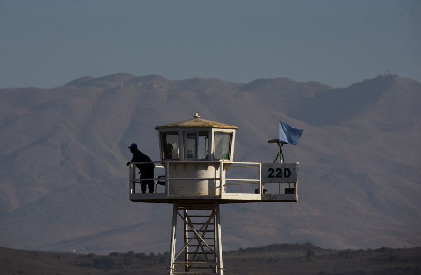 A United Nations peacekeeping soldier stands on an observation tower near the Quneitra border crossing between Israel and Syria (photo credit: REUTERS/Ronen Zvulun)