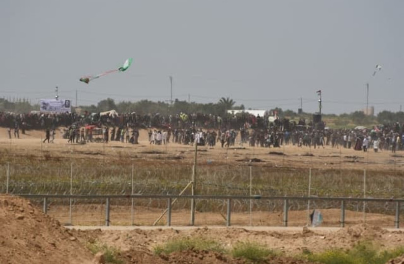 Gazan demonstrators launch a kite with a Molotov cocktail attached into Israeli territory. It lands within Gaza's borders (photo credit: IDF SPOKESPERSON'S UNIT)