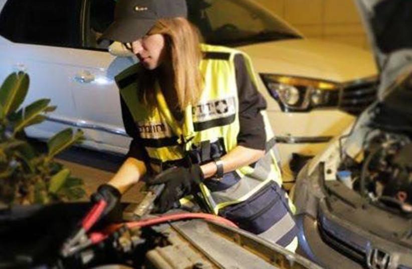 A female volunteer from Yedidim helps reset a car in the Tel Aviv suburb of Ramat Aviv (photo credit: YEDIDIM ISRAEL)