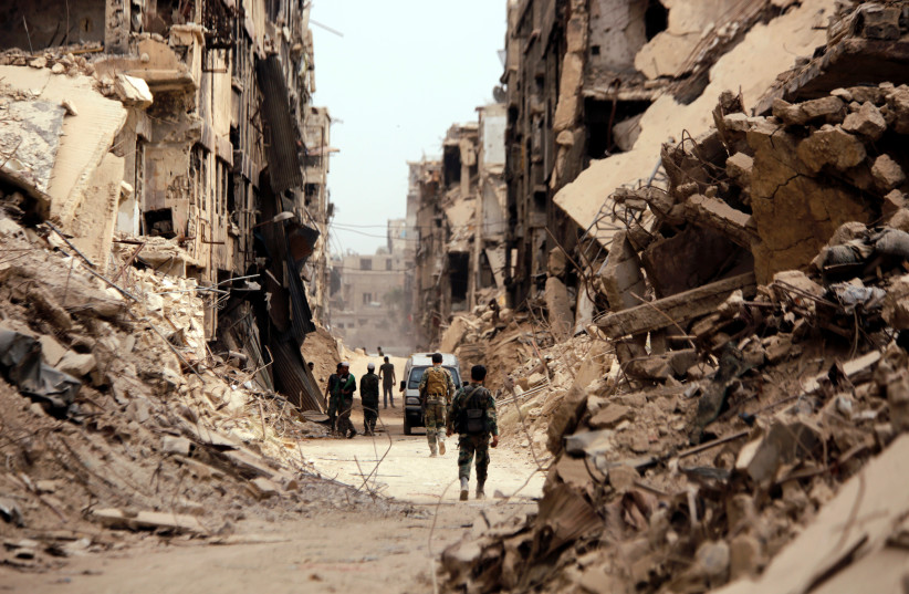 Soldiers walk past damaged buildings in Yarmouk Palestinian camp in Damascus (photo credit: OMAR SANADIKI/REUTERS)