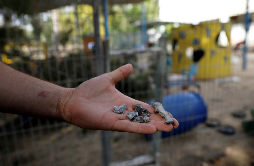 A man holds shrapnel from mortar shells fired from the Gaza Strip that landed near a kindergarten, in a Kibbutz on the Israeli side of the Israeli-Gaza border, May 29, 2018 (photo credit: AMIR COHEN/REUTERS)