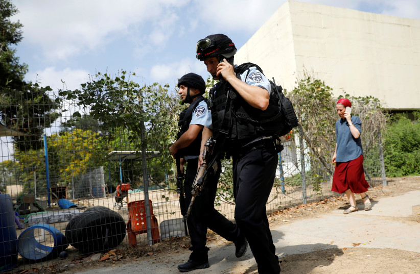 Israeli policemen walk past a kindergarten yard damaged by mortar shells fired from the Gaza Strip in a Kibbutz on the Israeli side of the Israeli-Gaza border, May 29, 2018. (photo credit: REUTERS/AMIR COHEN)