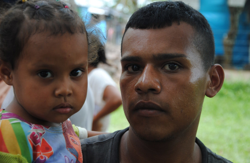 Ivan Carranza, 24, with his daughter, Maikelis, immigrants from Venezuela (photo credit: COURTESY CADENA)