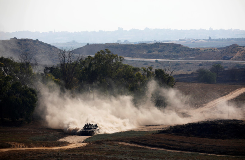 An Israeli tank drives on the Israeli side of the border between Israel and Gaza (photo credit: AMIR COHEN/REUTERS)