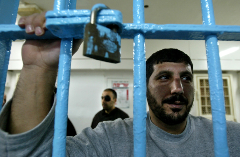 A Palestinian prisoner, convicted of security offences against Israel, looks out of his cell at Nitzan jail (photo credit: REUTERS/NIR ELIAS)