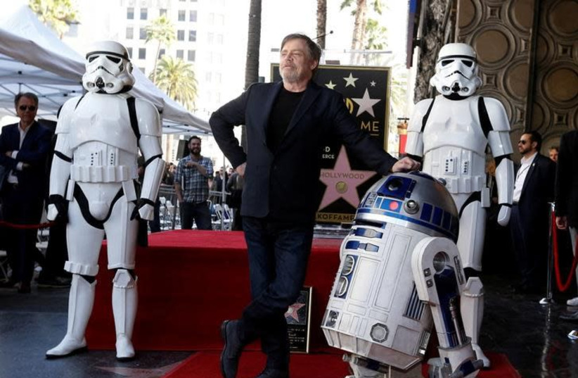 """Actor Mark Hamill poses with """"Star Wars"""" characters R2-D2 and Stormtroopers after unveiling his star on the Hollywood Walk of Fame in Los Angeles, California, US, March 8, 2018 (photo credit: MARIO ANZUONI/REUTERS)"""
