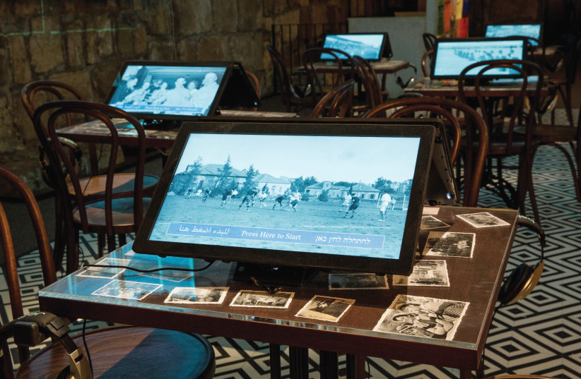 Laptops sit on the tables of the recreated Smadar Cinema cafe at the Tower of David exhibition. (photo credit: ODED ANTMAN)
