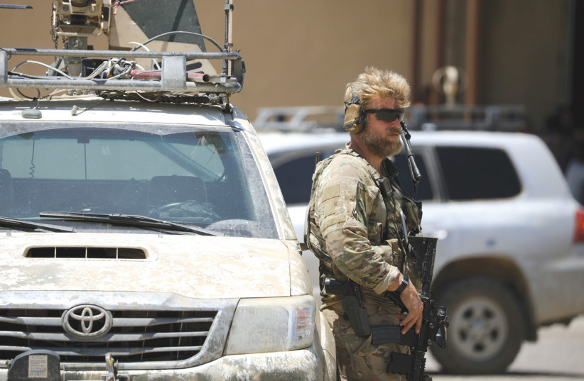 A US soldier guards a convoy with anti-ISIS envoy Brett McGurk in it last year. (photo credit: REUTERS)