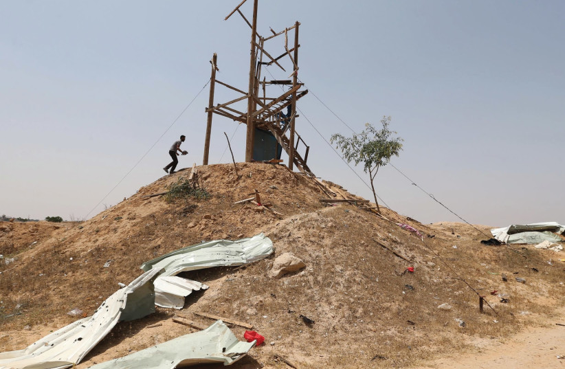PALESTINIANS INSPECT an Islamic Jihad observation post after it was targeted in Israeli tank shelling, in the southern Gaza Strip, May 2018. (photo credit: IBRAHEEM ABU MUSTAFA/REUTERS)