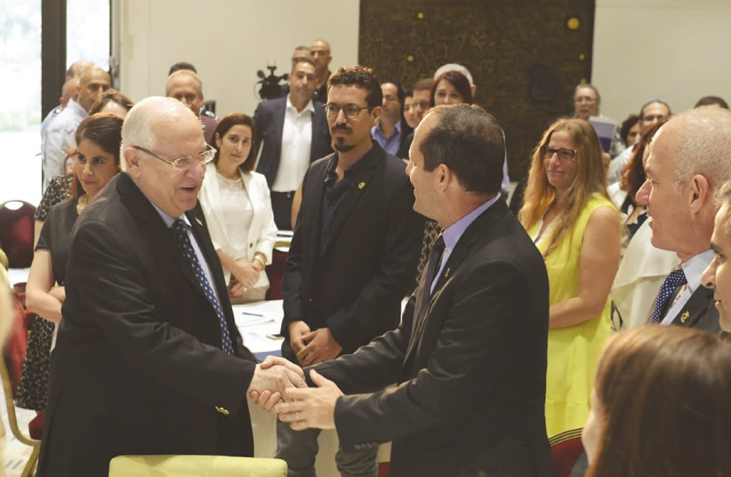 PRESIDENT REUVEN Rivlin (left) shakes hands with Jerusalem Mayor Nir Barkat at the President's Residence meeting yesterday to promote the betterment of east Jerusalem. (photo credit: Mark Neiman/GPO)