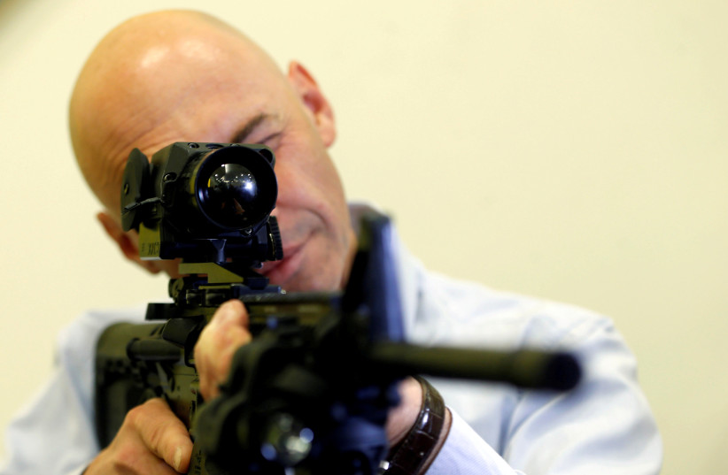 An employee looks through an infrared scope on a weapon at a preview presentation at Elbit Systems, Israel's biggest publicly listed defense firm (photo credit: REUTERS/BAZ RATNER)