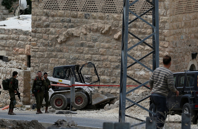 Israeli soldiers stand at the scene of an attempted ramming attack in Hebron, June 2, 2018.  (photo credit: REUTERS/MUSSA QAWASMA)