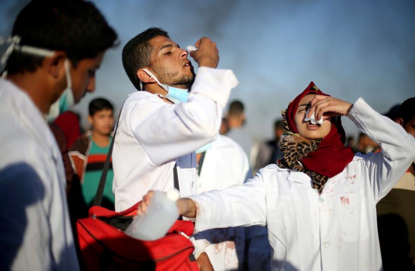 Female Palestinian medic Razan Al-Najar reacts to tear gas as she works at the scene of clashes at Israel-Gaza border, in the southern Gaza Strip, April 1, 2018 (photo credit: IBRAHEEM ABU MUSTAFA / REUTERS)