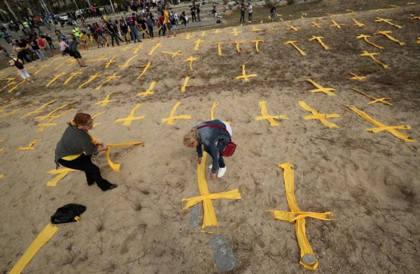 Catalan separatist supporters remove yellow crosses after a protest to demand the release of jailed Catalonian politicians, at Mataro's beach, north of Barcelona, Spain May 27, 2018 (photo credit: ALBERT GEA/ REUTERS)