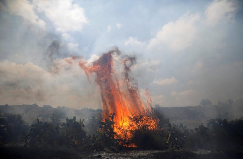 A fire burns in scrubland on the Israeli side of the border between Israel and the Gaza Strip, near kibbutz Gevaram (photo credit: AMIR COHEN/REUTERS)
