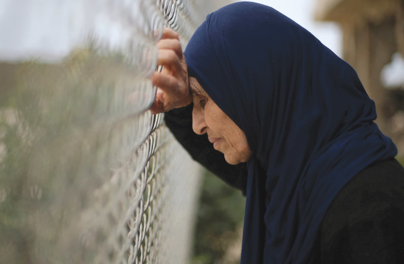 A Palestinian woman leans on a fence (photo credit: REUTERS)