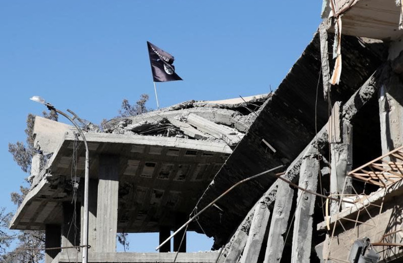 A flag of Islamic State militants is pictured above a destroyed house near the Clock Square in Raqqa, Syria October 18, 2017. Picture taken October 18, 2017. (photo credit: REUTERS/ERIK DE CASTRO)