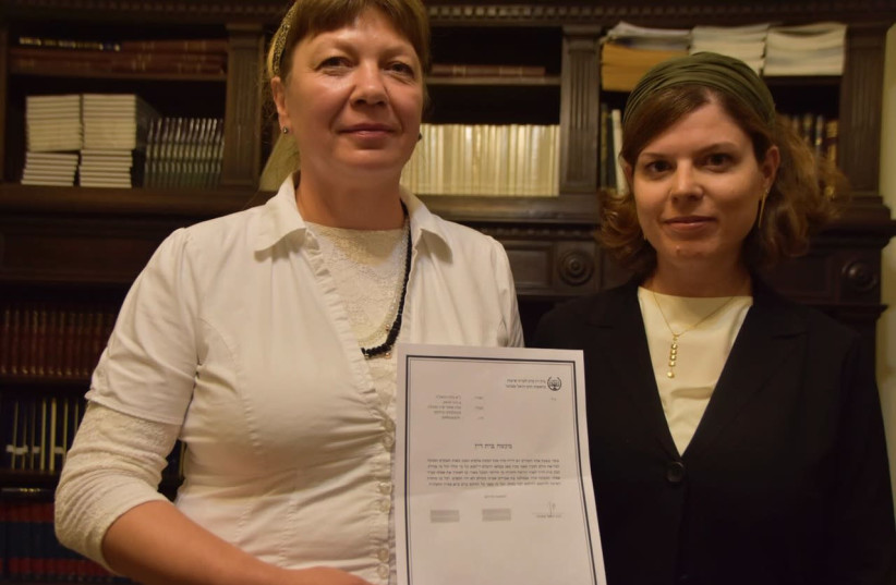 Zvia Gordestski (left) holding the rabbinical court document freeing her from her marriage, alongside Center for Women's Justice attorney Nitzan Caspi-Shiloni (photo credit: CENTER FOR WOMEN'S JUSTICE)