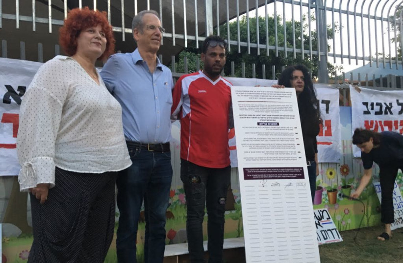 demonstrators hold a petition for rehabilitation of South Tel Aviv (photo credit: Courtesy)