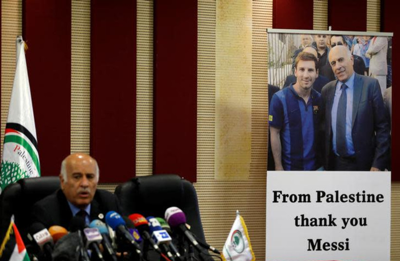 A poster of Palestinian FA chief Jibril Rajoub with Argentina's soccer player Lionel Messi is seen during Rajoub's news conference, in Ramallah in the West Bank June 6, 2018. (photo credit: REUTERS/MOHAMAD TOROKMAN)