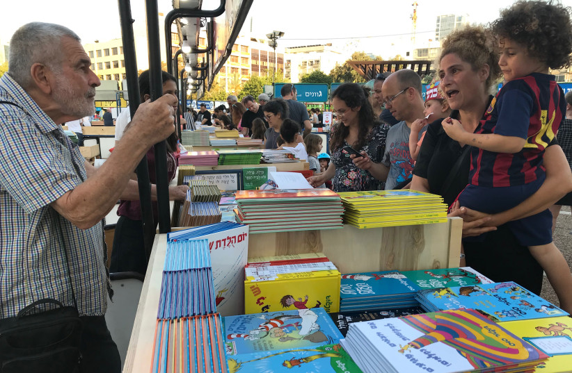 Readers check out this year's selection of books at Tel Aviv's Book Week at Rabin Square on June 6, 2018 (photo credit: Courtesy)