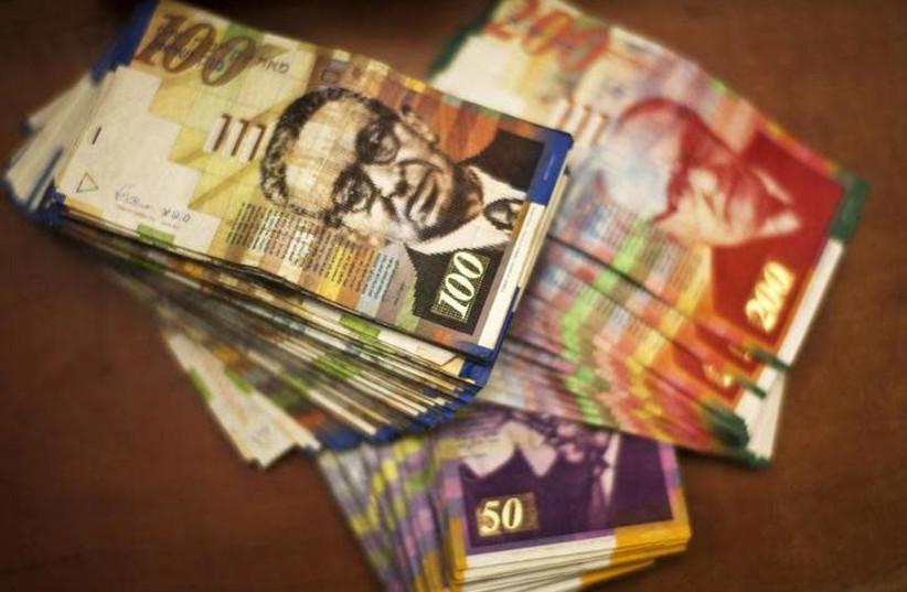 Stacks of Israeli shekel notes [Illustrative] (photo credit: NIR ELIAS / REUTERS)