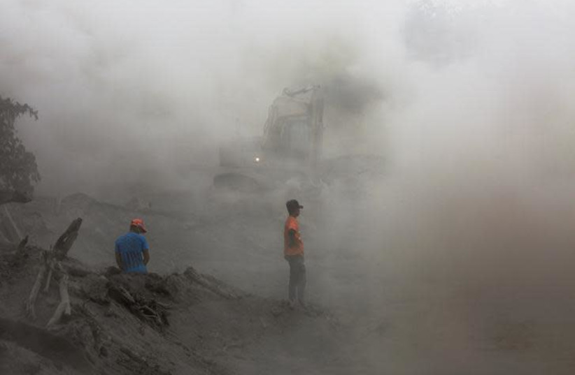 Residents are seen amidst ashes as heavy machinery removes ash from a road at an area affected by the eruption of the Fuego volcano at El Rodeo in Escuintla, Guatemala June 6, 2018. Picture taken June 6, 2018. (photo credit: REUTERS/CARLOS JASSO)