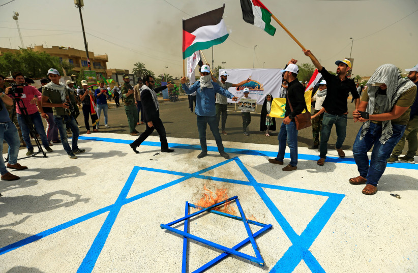 Iraqi Shi'ite Muslims burn a Star of David during a parade marking the annual al-Quds Day, (Jerusalem Day) on the last Friday of the Muslim holy month of Ramadan in Baghdad, Iraq June 8, 2018. (photo credit: THAIER AL-SUDANI/REUTERS)
