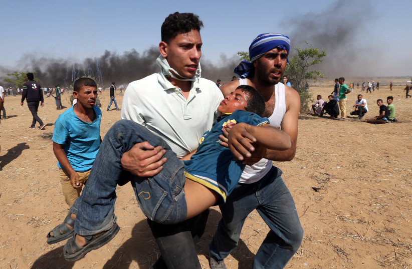 A wounded Palestinian boy is evacuated during a protest marking al-Quds Day, (Jerusalem Day), at the Israel-Gaza border in the southern Gaza Strip June 8, 2018. (photo credit: IBRAHEEM ABU MUSTAFA / REUTERS)