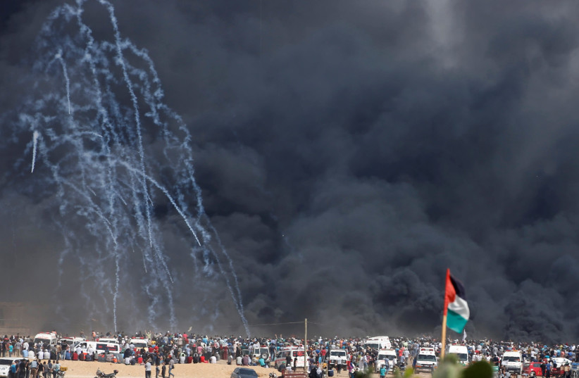 Tear gas canisters are fired by Israeli troops at Palestinian demonstrators during a protest marking al-Quds Day, (Jerusalem Day), at the Israel-Gaza border east of Gaza City June 8, 2018. (photo credit: MOHAMMED SALEM/ REUTERS)
