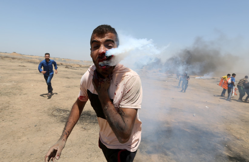 A wounded Palestinian demonstrator reacts as he is hit in the face with a tear gas canister fired by Israeli troops during a protest marking al-Quds Day, (Jerusalem Day), at the Israel-Gaza border in the southern Gaza Strip June 8, 2018. (photo credit: IBRAHEEM ABU MUSTAFA / REUTERS)