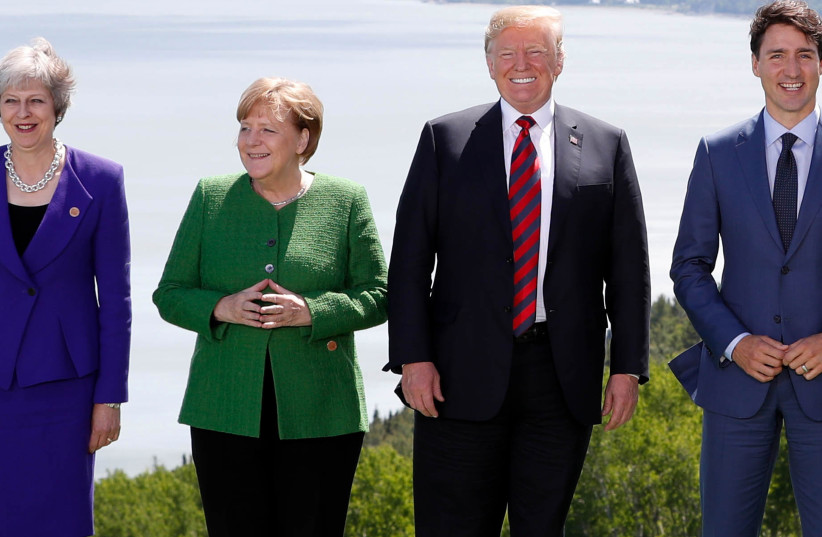 Britain's Prime Minister Theresa May, Germany's Chancellor Angela Merkel, US President Donald Trump and Canada's Prime Minister Justin Trudeau pose during a family photo at the G7 Summit in the Charlevoix city of La Malbaie, Quebec, Canada, June 8, 2018 (photo credit: YVES HERMAN / REUTERS)