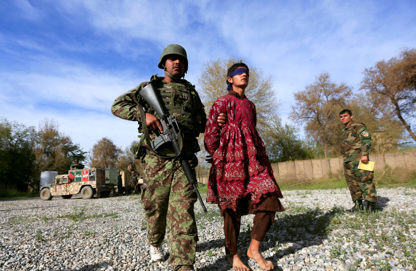 An Afghan soldier escorts a Taliban militant, who was arrested by Afghan security forces, and then presented to the media, in Jalalabad, Afghanistan March 17, 2018 (photo credit: REUTERS/PARWIZ)