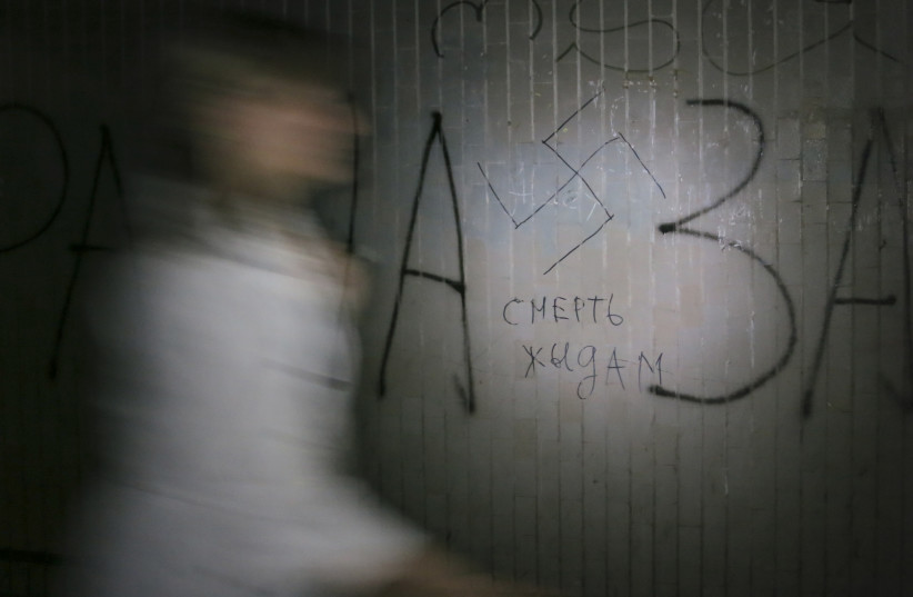 "A woman walks past a swastika and the inscription ""Death to Jews' painted on a wall in an underpass in Kiev May 29, 2012.  (photo credit: GLEB GARANICH/REUTERS)"