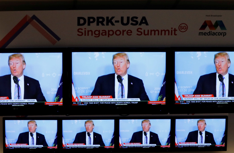 A TV news reports about U.S. President Donald Trump is projected on TV sets at a media center for the summit between the U.S and North Korea in Singapore (photo credit: REUTERS/KIM KYUNG-HOON)