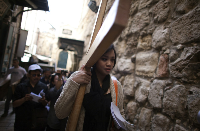 An Indonesian Christian worshipper holds a cross as she walks the Via Dolarosa on Good Friday in Jerusalem's Old City April 6, 2012. Christian worshippers retraced the route Jesus took along Via Dolorosa to his crucifixion in the Church of the Holy Sepulchre. (photo credit: DARREN WHITESIDE / REUTERS)