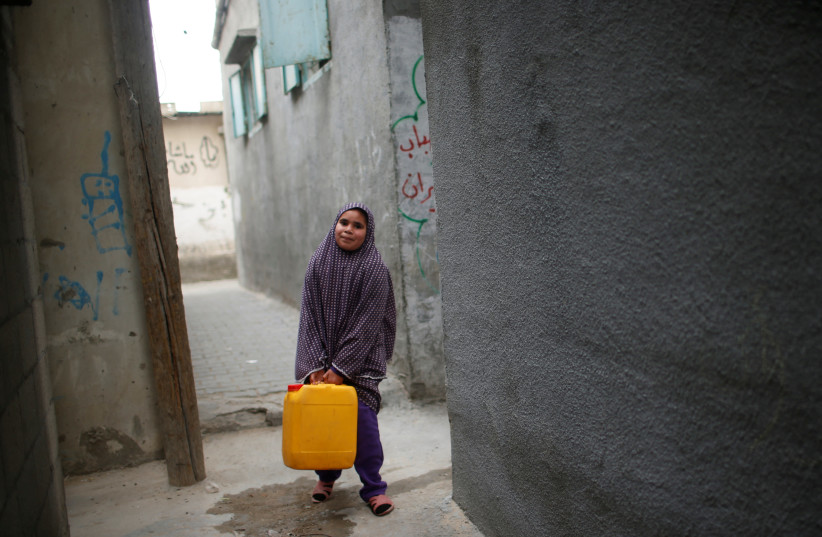 A Palestinian girl carries a potable water container after filling it from a public tap in Jabaliya refugee camp in the northern Gaza Strip (photo credit: MOHAMMED SALEM/REUTERS)