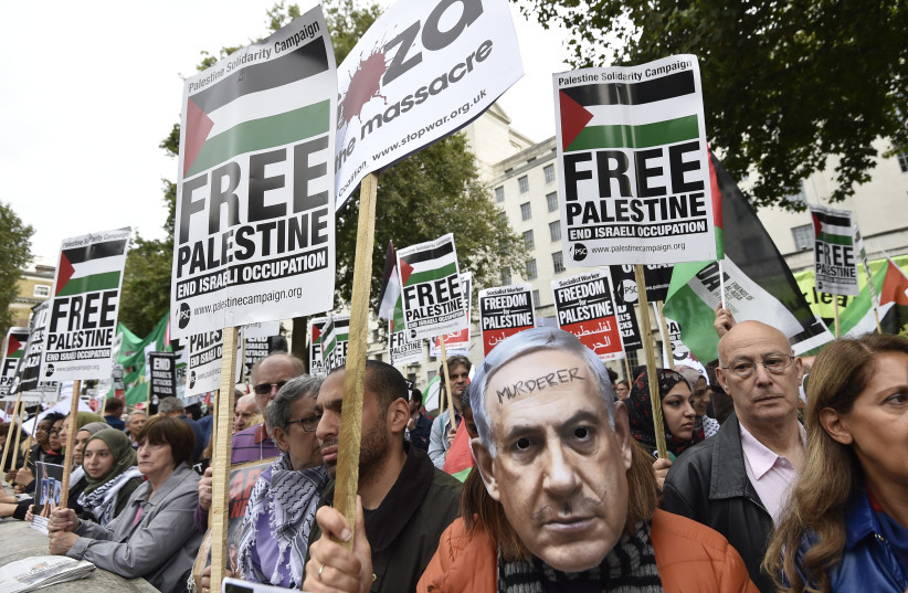 A demonstrator wears a Benjamin Netanyahu mask with a message written on it during a protest outside Downing Street in London, Britain September 9, 2015 (photo credit: REUTERS/TOBY MELVILLE)