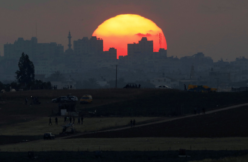 The sun sets over the Gaza Strip, as seen from the Israeli side of the border May 15, 2018 (photo credit: REUTERS/AMIR COHEN)