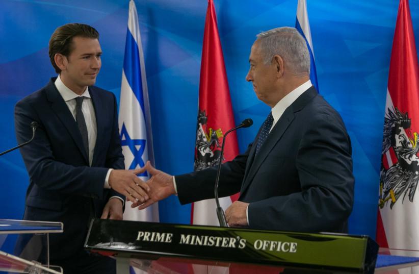 Prime Minister Benjamin Netanyahu (R) shakes hands with Austrian Chancellor Sebastian Kurz (L) during a meeting on June 11, 2018 (photo credit: OHAD TZVEIGENBERG/POOL)